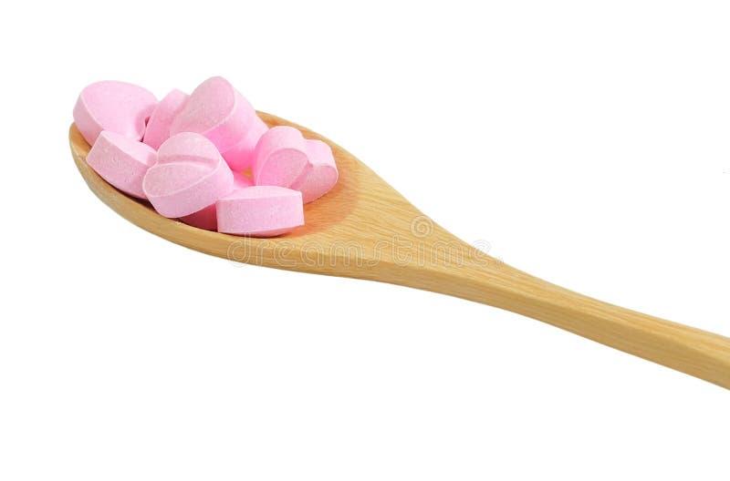 Cuchara de madera por completo con las vitaminas C en el fondo blanco imagen de archivo libre de regalías