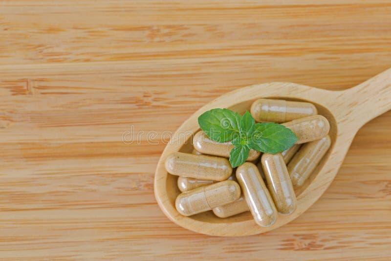 Cuchara de madera por completo de la medicina herbaria en cápsulas claras, FO ideales foto de archivo