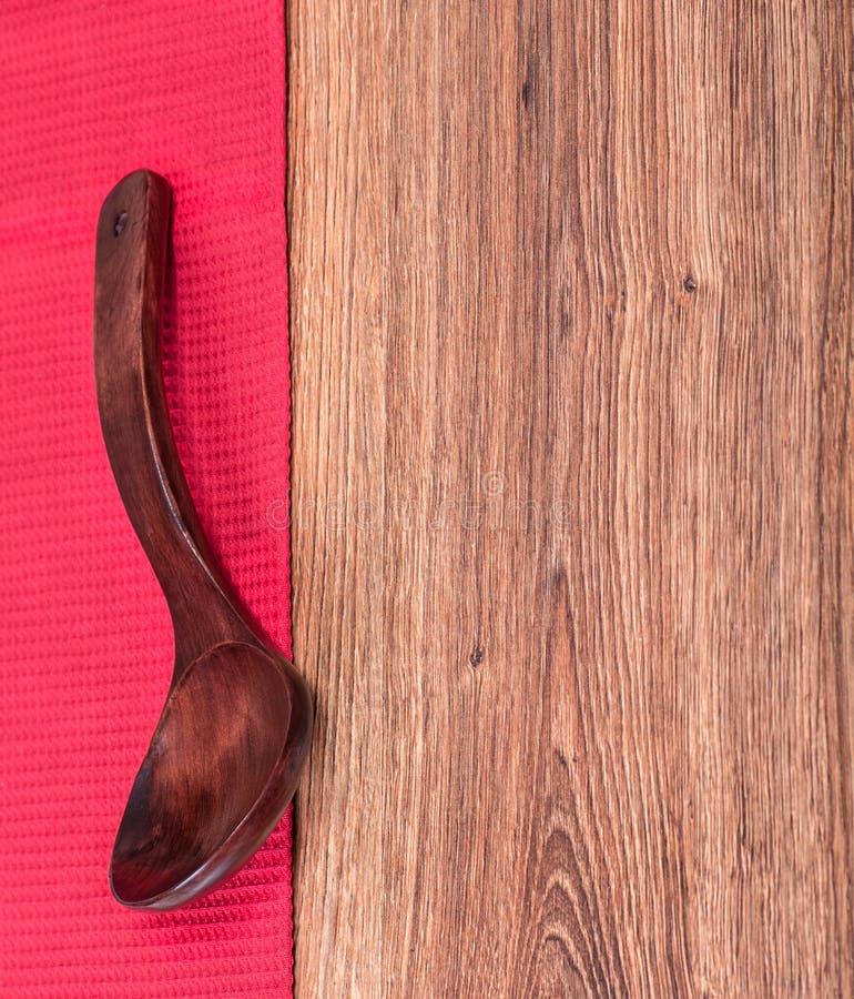 Cuchara de madera roja en una toalla roja imagen de archivo
