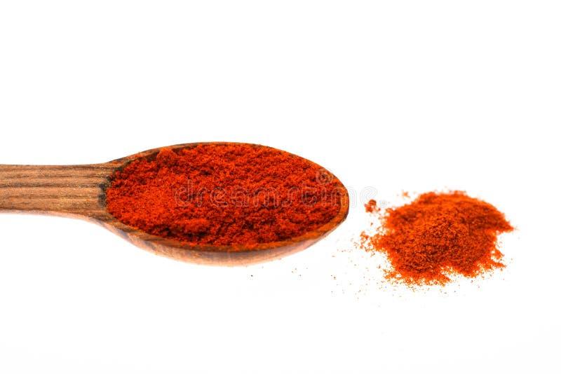 Cuchara llenada del polvo de tierra de la pimienta roja Condimentos y concepto de las especias Cuchara hecha fuera de madera por  imagen de archivo libre de regalías