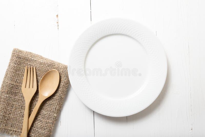 Cuchara y bifurcación de madera con el plato imágenes de archivo libres de regalías