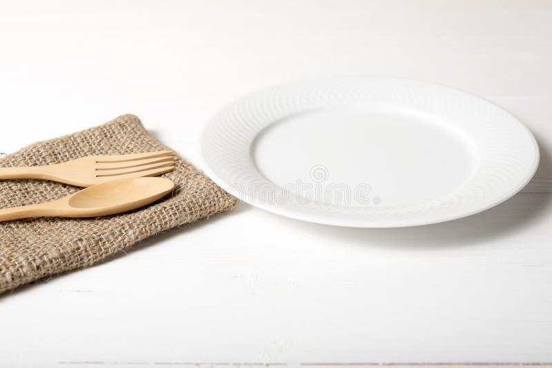 Cuchara y bifurcación de madera con el plato foto de archivo