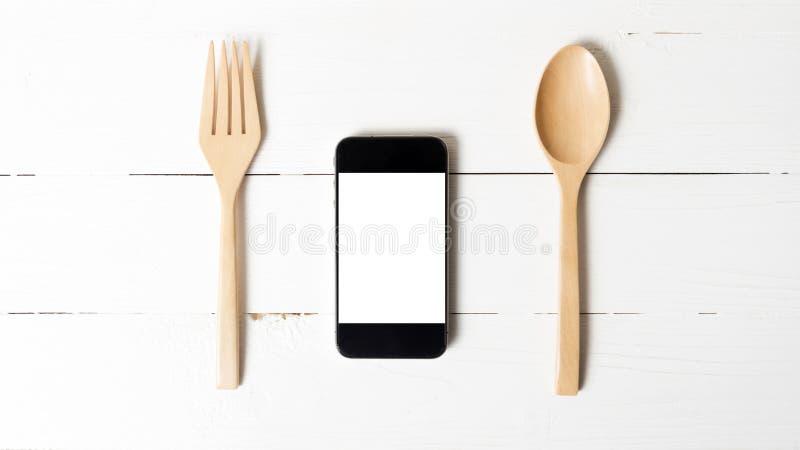 Cuchara y concepto elegante del teléfono que comen al social foto de archivo libre de regalías