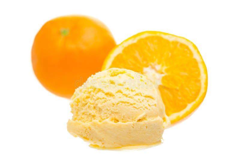 Cucharada anaranjada del helado con las naranjas en el fondo blanco imagen de archivo