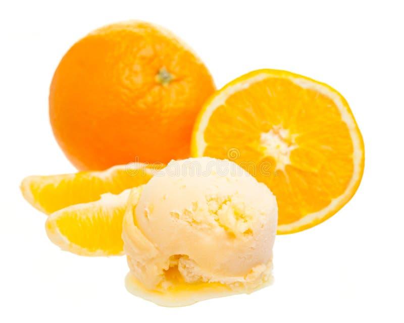 Cucharada anaranjada del helado delante de la naranja entera y una rebanada de naranja aislada en el fondo blanco imagenes de archivo