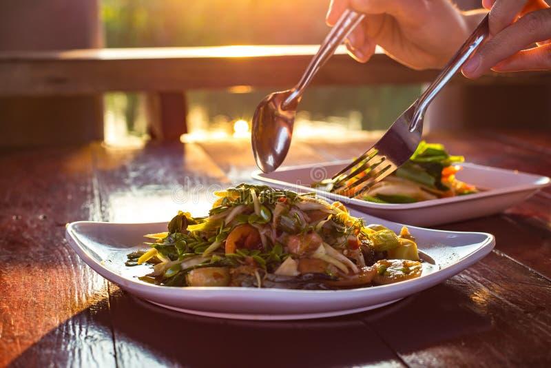Cucharada de la mano encima de la ensalada picante de la papaya llamada 'Somtum 'en tailandés en la tabla de madera con el rayo d imágenes de archivo libres de regalías