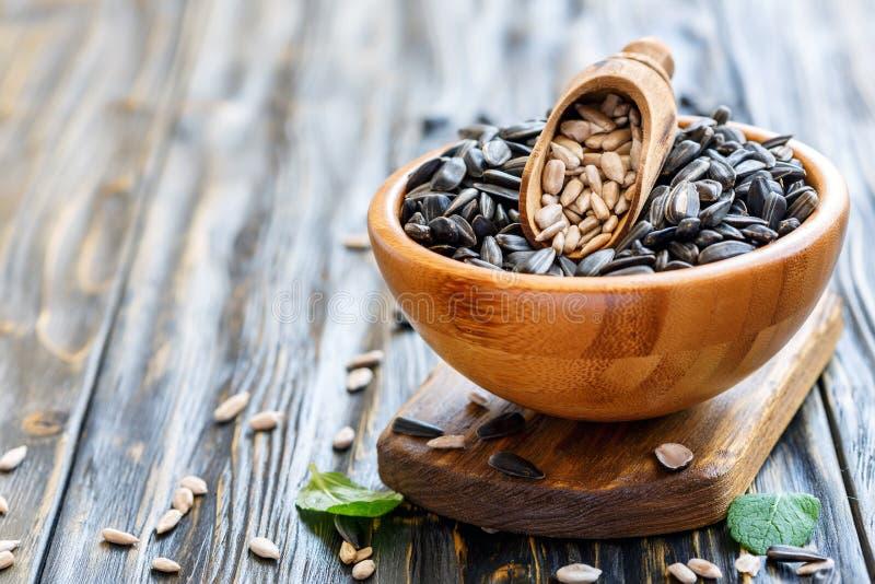 Cucharada de madera con las semillas limpiadas en cuenco con las semillas de girasol fotos de archivo libres de regalías