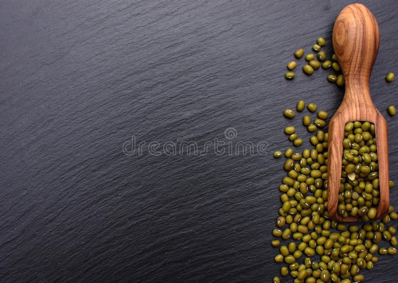 Cucharada de madera en el fondo de un tablero de piedra negro, lugar de las habas para el texto, haba de mung fotos de archivo libres de regalías