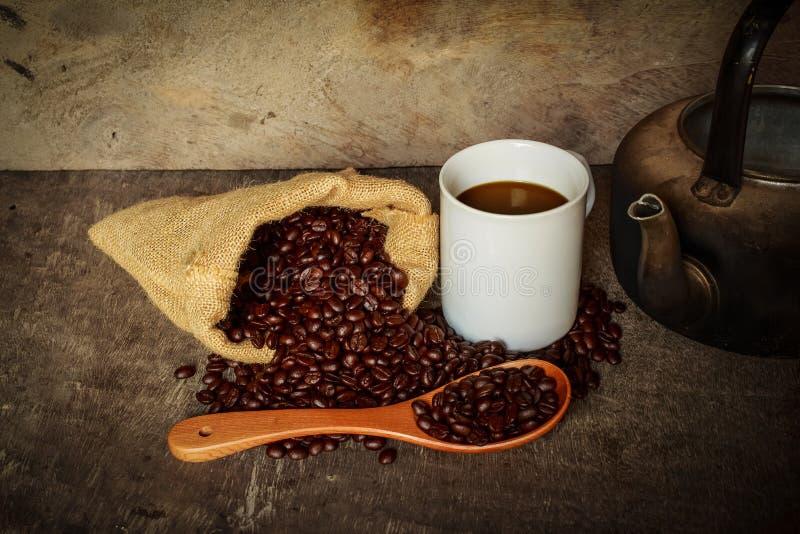 Cucharada del saco de la taza de café de los granos y de la caldera de café en la madera vieja imagen de archivo libre de regalías