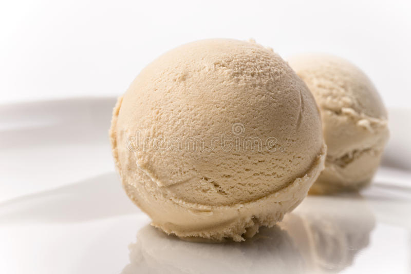 Cucharada quemada del helado del café de la nata en fondo del blanco de la placa imagenes de archivo