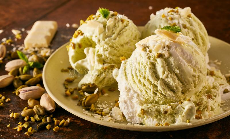 Cucharadas del helado gastrónomo del pistacho en plato imagenes de archivo