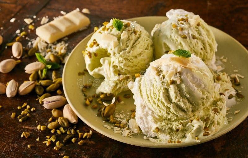 Cucharadas del helado gastrónomo del pistacho en plato fotografía de archivo