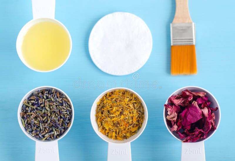 Cucharadas plásticas con el aceite de oliva y las diversas hierbas curativas - flores color de rosa secas de la maravilla, de la  fotografía de archivo libre de regalías