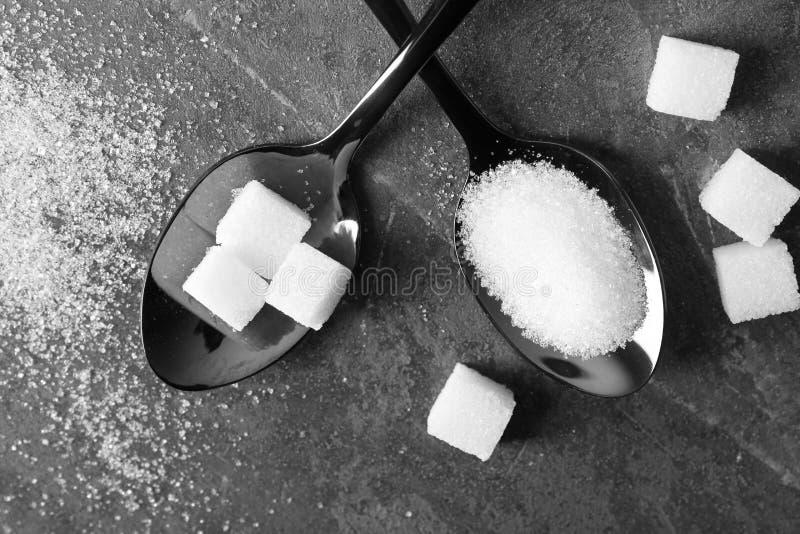 Cucharas con el azúcar en la tabla gris imágenes de archivo libres de regalías