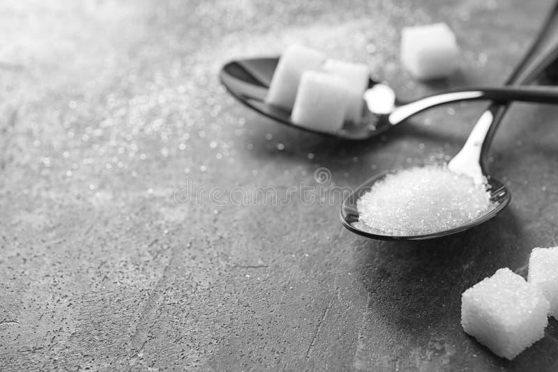 Cucharas con el azúcar en la tabla gris fotografía de archivo libre de regalías