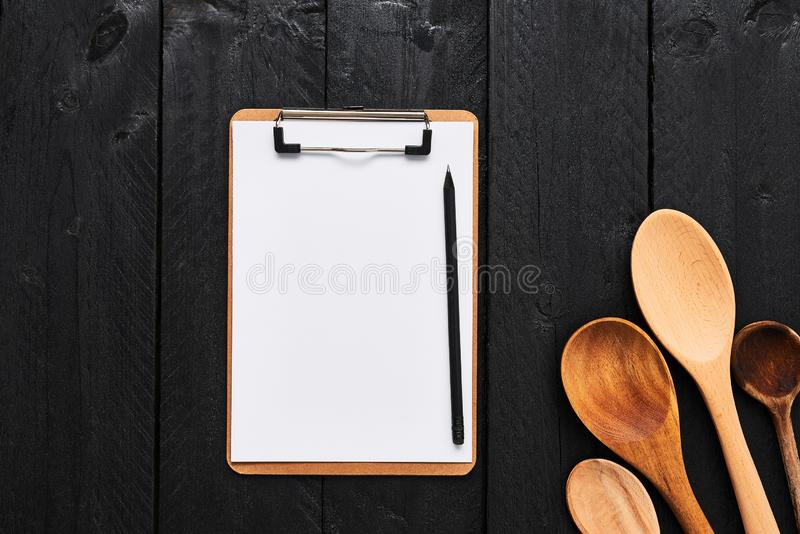 Cucharas de madera con el tablero en blanco de la cartulina para el menú fotos de archivo