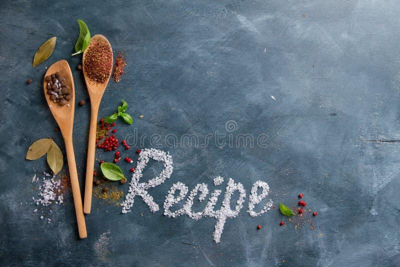 Cucharas de madera con las especias y palabra de la receta foto de archivo