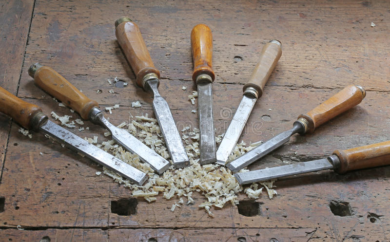cuchillas de acero agudas muchos cinceles y chippings del serrín en Workben imagenes de archivo