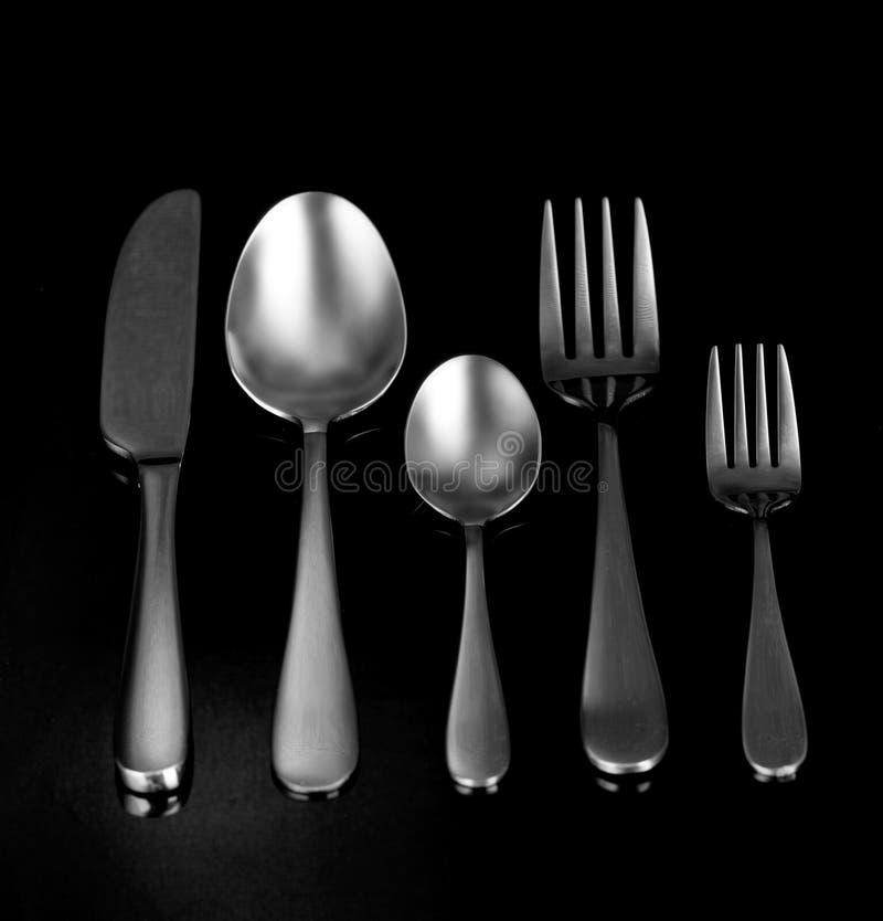 Cuchillería de plata, en fondo negro imagen de archivo libre de regalías