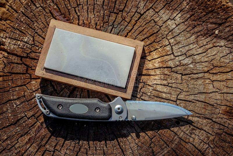 Cuchillo afilado y muela en un fondo de madera fotografía de archivo libre de regalías