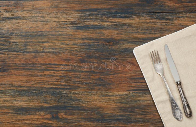 Cuchillo, bifurcación y toalla en la tabla de madera fotos de archivo libres de regalías