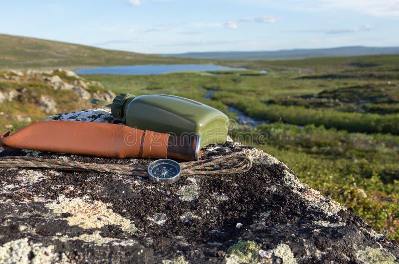 Cuchillo, compás y mapa en la roca foto de archivo