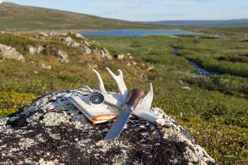 Cuchillo, compás y mapa en la roca fotografía de archivo