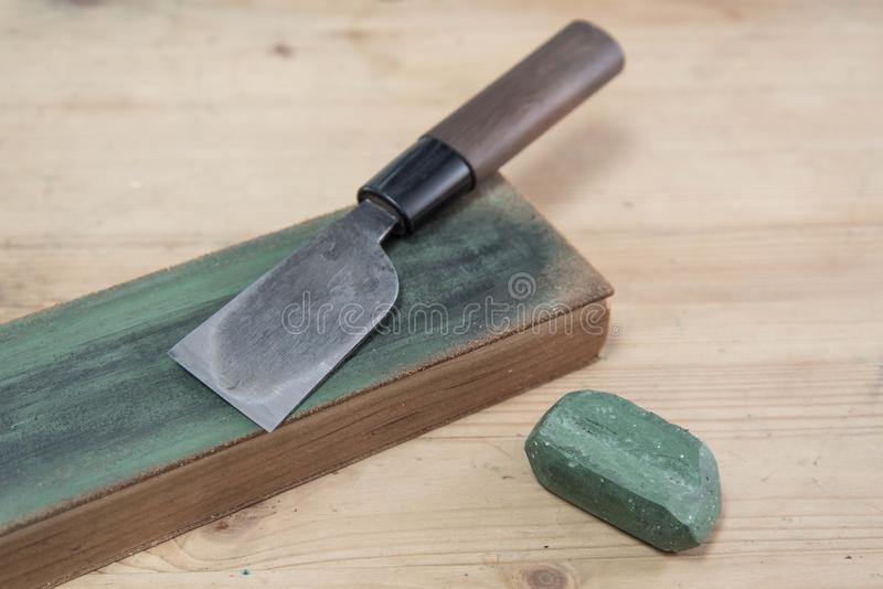 Cuchillo de cuero japonés del arte en un suavizador de cuero del cuchillo con el compuesto de pulido del verde en una superficie  imagenes de archivo