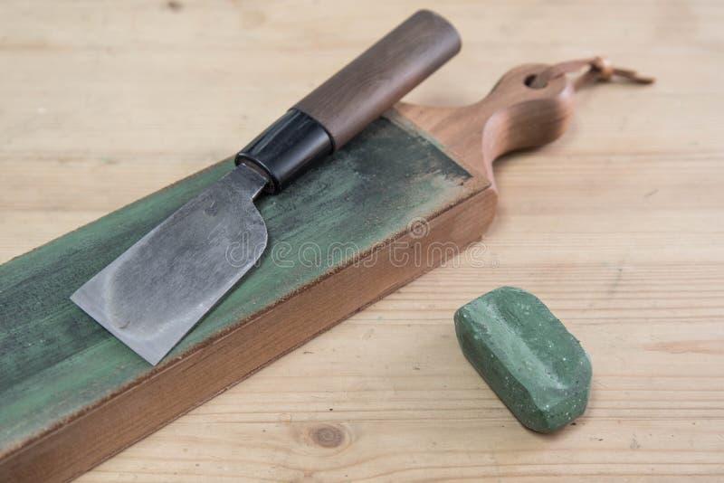 Cuchillo de cuero japonés del arte en un suavizador de cuero del cuchillo con el compuesto de pulido del verde en una superficie  fotos de archivo