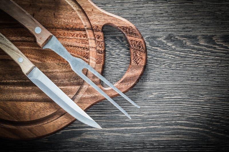 Cuchillo de la bifurcación de la carne que talla al tablero en el fondo de madera imagen de archivo