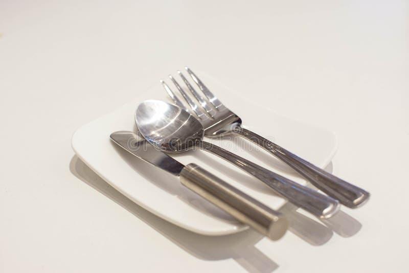 Cuchillo de la bifurcación, de la cuchara y de mantequilla en una placa blanca foto de archivo