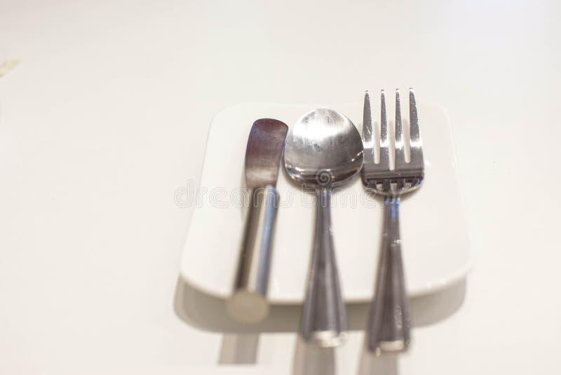 Cuchillo de la bifurcación, de la cuchara y de mantequilla en una placa blanca imágenes de archivo libres de regalías