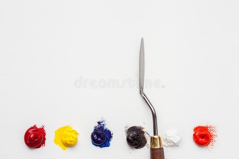 Cuchillo de paleta y pintura de aceite en la lona de lino del artista foto de archivo