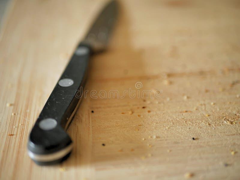Cuchillo de pelado en tabla de cortar de la cocina fotos de archivo libres de regalías