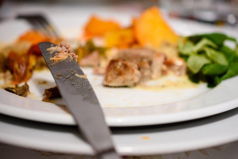 Cuchillo del acero inoxidable al lado de la placa con el filete parcialmente consumido del cerdo con las patatas y la ensalada co fotos de archivo