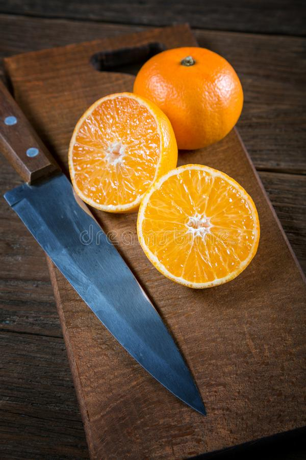 Cuchillo del corte de la mandarina en una tabla vieja fotos de archivo libres de regalías