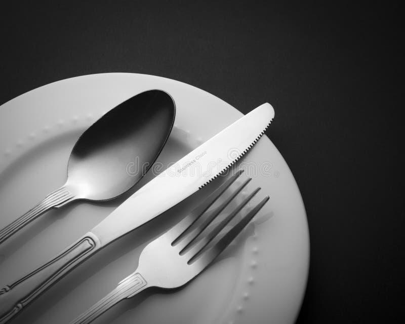 Cuchillo determinado y cuchara de la bifurcación de los cubiertos aislados en los utensilios blancos de la cocina de la placa imagenes de archivo