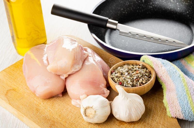 Cuchillo en el sart?n, aceite vegetal, pedazos de pechuga de pollo cruda, ajo, cuenco con el condimento en tabla de cortar en la  foto de archivo libre de regalías
