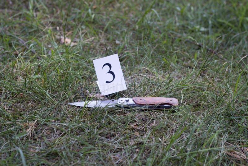 Cuchillo en la hierba, investigación, asesinato imagen de archivo