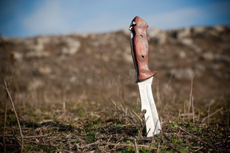 Cuchillo en la tierra imagen de archivo