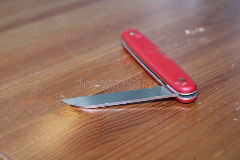 Cuchillo militar suizo rojo en el cierre de madera de la superficie para arriba imagen de archivo libre de regalías