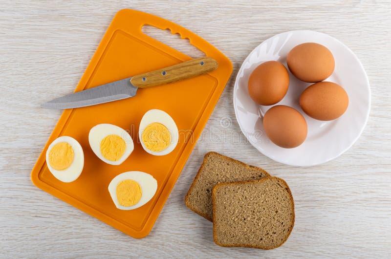 Cuchillo, mitades de los huevos pelados en tabla de cortar, pedazos de pan, huevos en placa en la tabla de madera Visi?n superior imagen de archivo libre de regalías