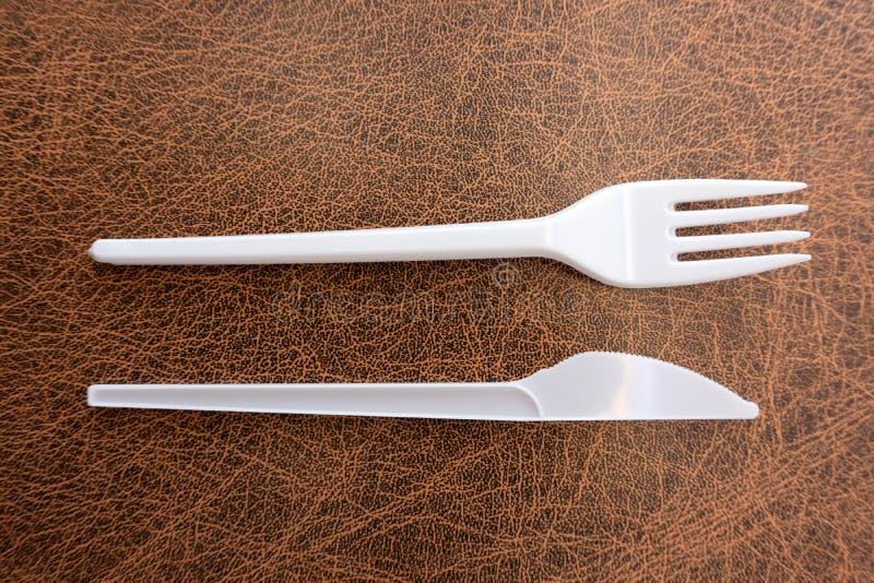 Cuchillo plástico y bifurcación aislados en el fondo blanco imagenes de archivo
