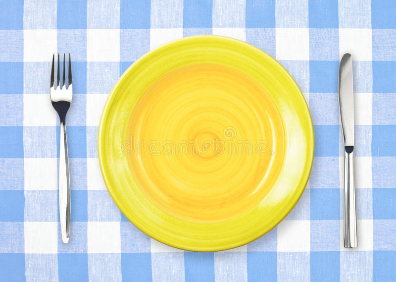 Cuchillo, placa amarilla y fork en mantel controlado fotografía de archivo