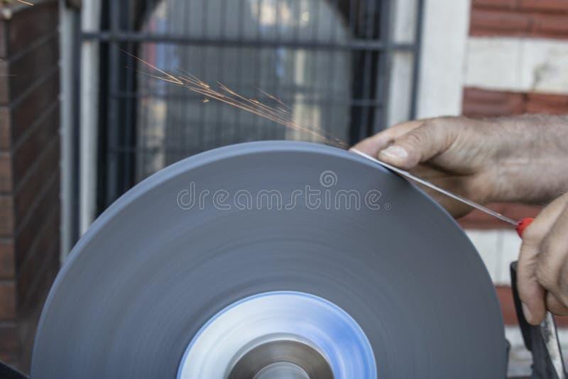Cuchillo que afila la mano y que enarena el primer de la máquina fotos de archivo libres de regalías