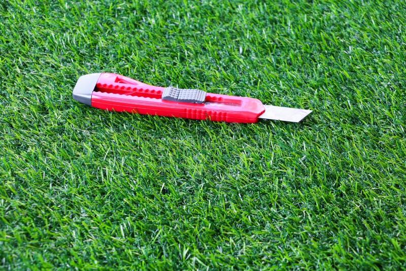 Cuchillo rojo del cortador en fondo artificial de la hierba foto de archivo libre de regalías