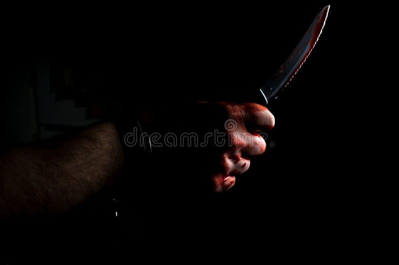 Cuchillo sangriento de la mano foto de archivo libre de regalías
