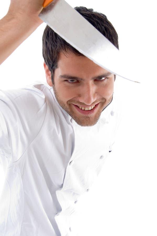 Cuchillo sonriente de la explotación agrícola del cocinero de sexo masculino joven hermoso imagen de archivo