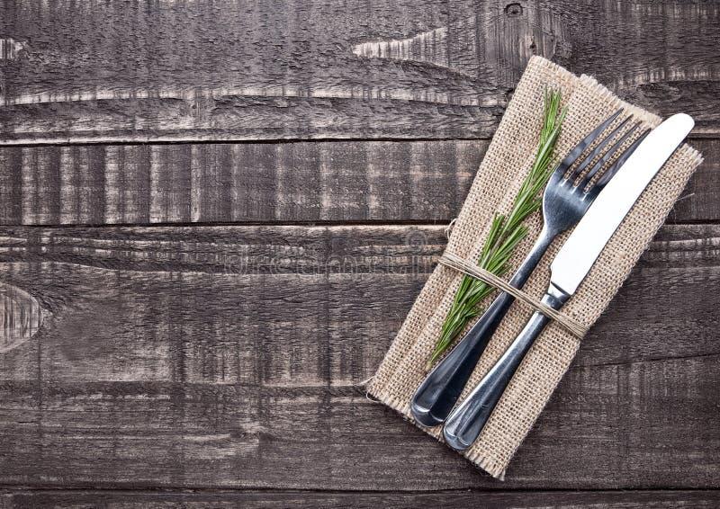 Cuchillo y bifurcación dentro de la toalla de cocina en el tablero de madera imagenes de archivo