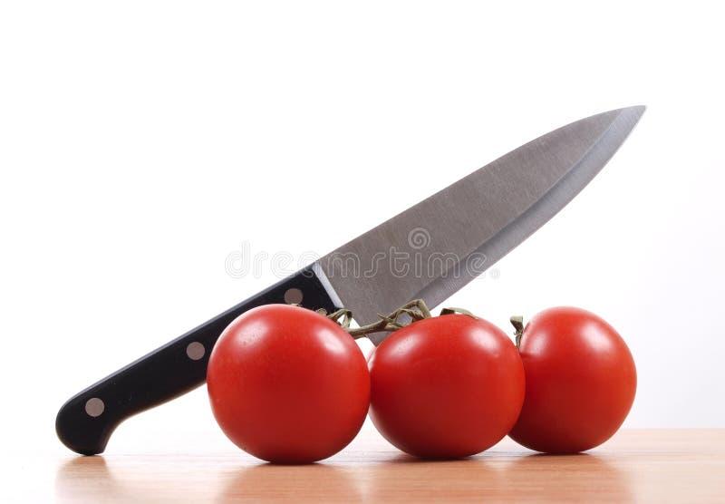 Cuchillo y tomate dos foto de archivo